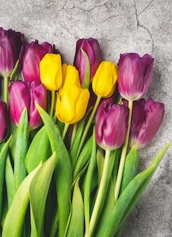 Ramo de tulipanes morados y amarillos sobre una mesa gris