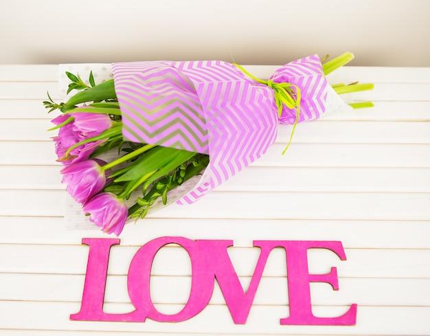 Ramo de tulipanes morados sobre mesa blanca, letras de madera amor