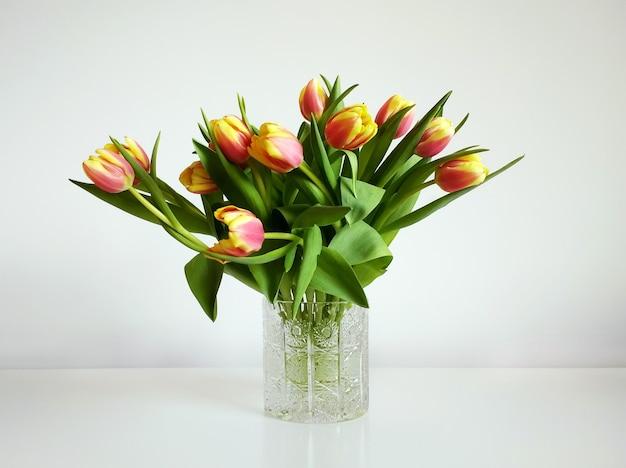 Ramo de tulipanes naranjas en un jarrón bajo las luces sobre un fondo blanco.