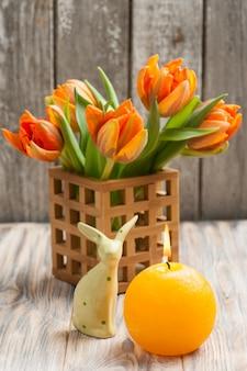 Ramo de tulipanes naranjas, velas encendidas y conejitos de pascua