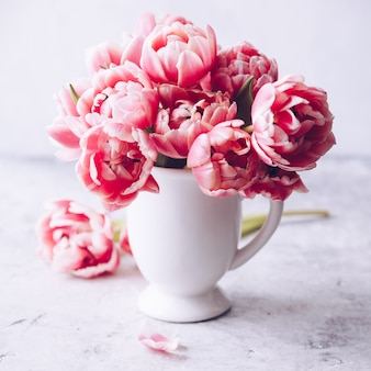 Ramo de tulipanes de primavera en florero sobre fondo shabby chic