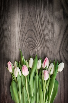 Ramo de tulipanes de primavera en madera