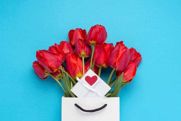 Ramo de tulipanes rojos brillantes, una pequeña caja de regalo blanca con un corazón rojo en una bolsa de regalo blanca sobre un azul. concepción de felicitaciones y un regalo. vista plana, vista superior