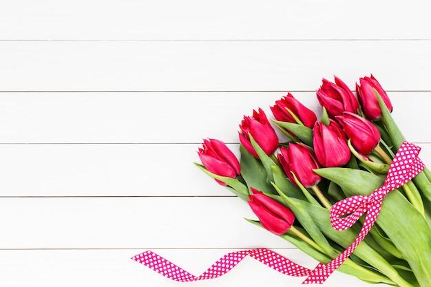 Ramo de tulipanes rojos decorado con cinta. copia espacio
