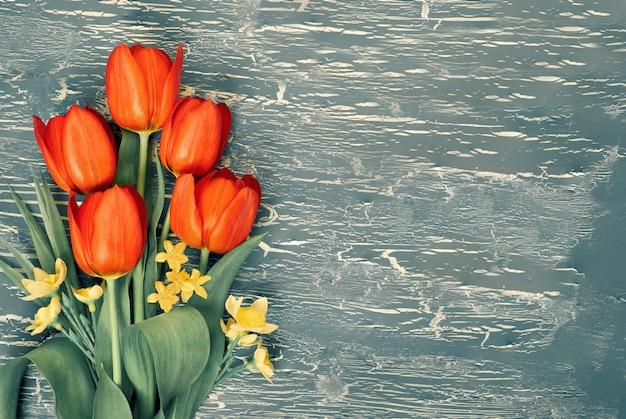 Ramo de tulipanes rojos y flores de lirio de los valles sobre fondo rústico