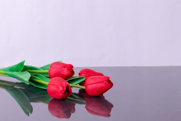 Ramo de tulipanes rojos en mesa con reflejo