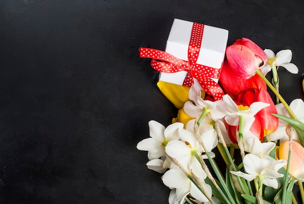 Ramo de tulipanes rojos, narcisos y regalo sobre fondo negro