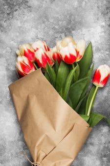 Ramo de tulipanes rosados blancos sobre un fondo gris. vista superior