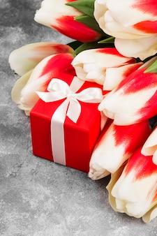 Ramo de tulipanes rosados blancos sobre un fondo gris