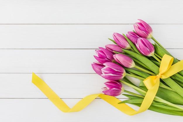 Ramo de tulipanes rosados brillantes adornados con la cinta amarilla en el fondo de madera blanco. vista superior, copia espacio