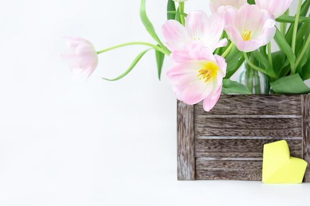 Un ramo de tulipanes rosados en una caja de madera y un corazón de papel amarillo en un fondo blanco.