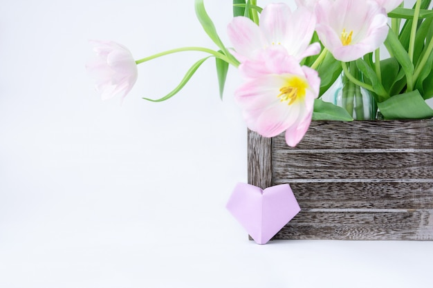 Un ramo de tulipanes rosados en una caja de madera y un corazón del papel del ciruelo en un fondo blanco.