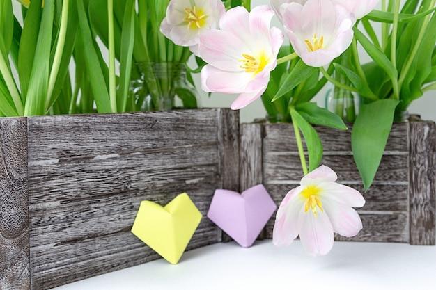 Un ramo de tulipanes rosados en una caja de madera y dos corazones de papel de color amarillo y lila sobre un fondo blanco.