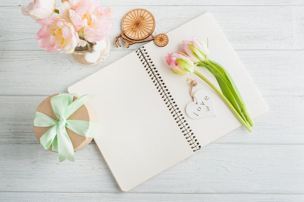 Ramo de tulipanes rosados y cuaderno abierto