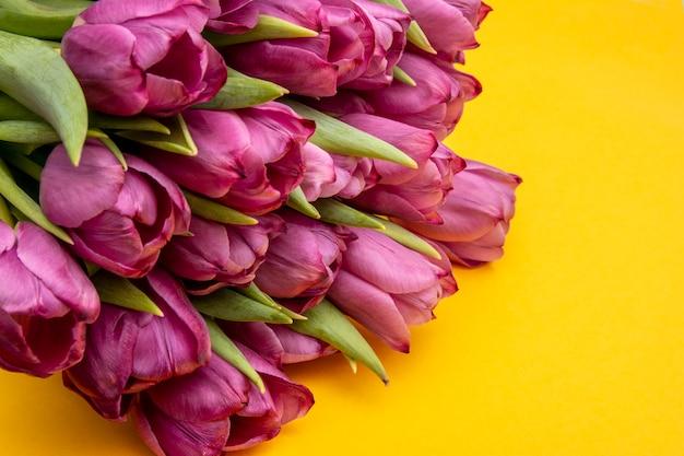 Ramo de tulipanes rosados / fondo del día de pascua. ramo de tulipanes sobre un fondo amarillo, banner web