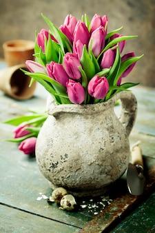 Ramo de tulipanes rosados, huevos de pascua y herramientas de jardinería