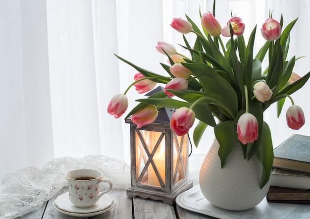 Un ramo de tulipanes rosados en un jarrón, libros, una vela y una taza de café.