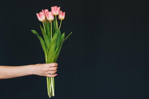 Ramo de tulipanes rosados en mano de mujer