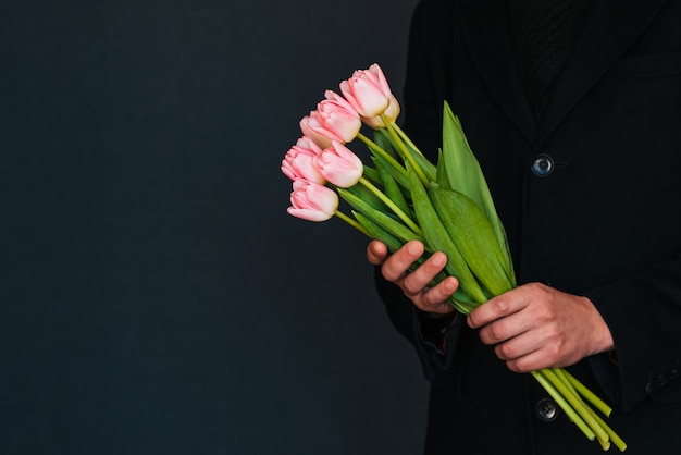 Ramo de tulipanes rosados en manos de un hombre con un abrigo negro