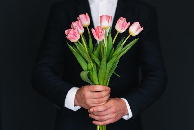 Ramo de tulipanes rosados en manos de hombres con traje azul