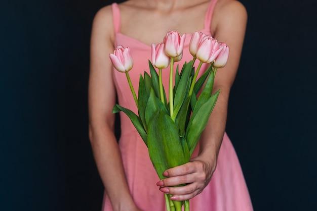 Ramo de tulipanes rosados en manos de mujeres