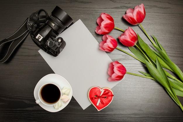 Ramo de tulipanes rosados, una taza de café, galletas rojas en forma de corazón con una nota, cámara réflex digital y hoja de papel