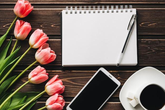 Ramo de tulipanes rosados con una taza de café y un teléfono inteligente en una mesa de madera