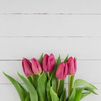 Ramo de tulipanes sobre fondo de madera