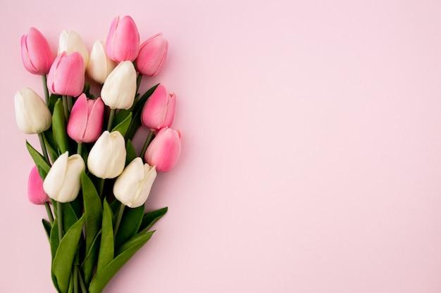 Ramo de tulipanes sobre fondo rosa con copyspace