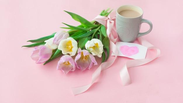 Ramo de tulipanes y una taza de café en un fondo en colores pastel rosado.