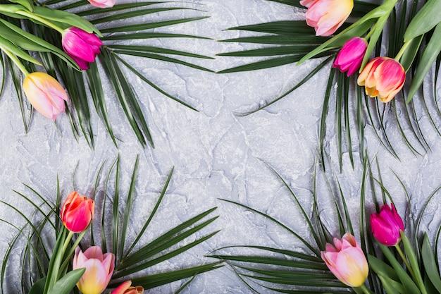 Ramos de tulipanes y hojas de palmera.