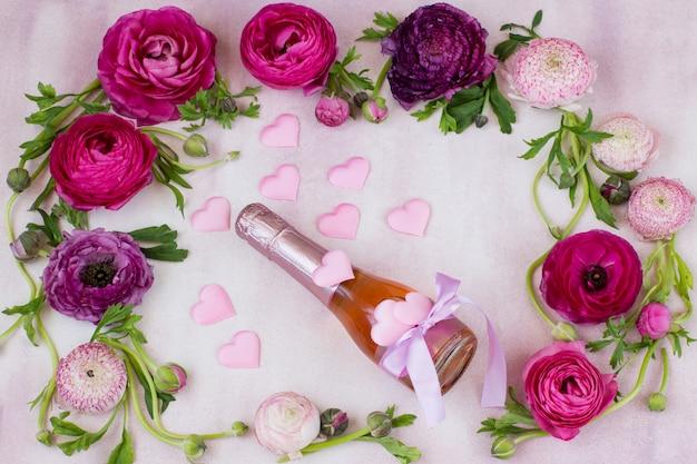 Un ranúnculo y una botella de champán y corazones rosados de satén.