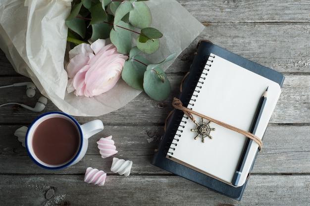 Ranúnculo rosa, cuaderno abierto y bicicleta