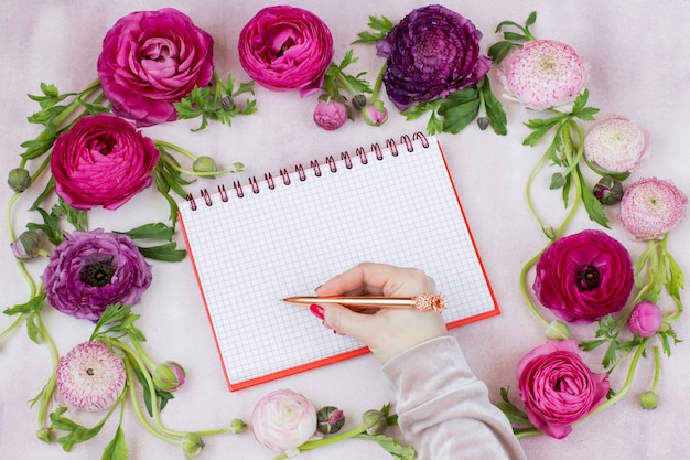 Ranunculus, mano de mujer, pluma y cuaderno en blanco