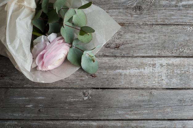 Ranunculus rosa sobre fondo de madera