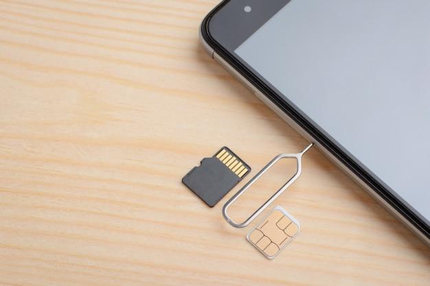 Ranura de apertura para tarjeta sim y tarjeta de memoria micro sd en un teléfono inteligente moderno con clip especial