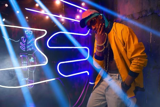 Rapero negro, músico en club con luces de neón