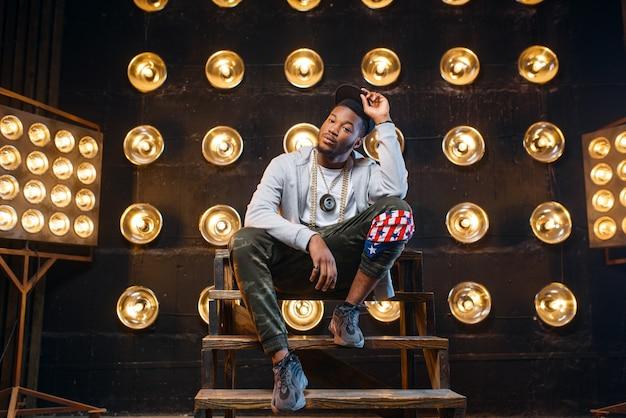 Rapero negro en poses de gorra, actuación en el escenario con focos