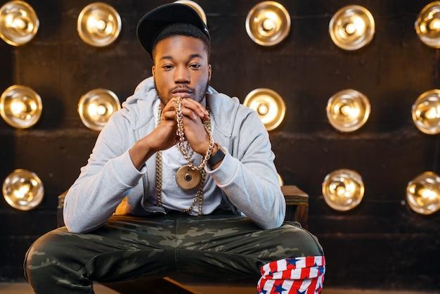 Rapero negro en poses de gorra, actuación en el escenario
