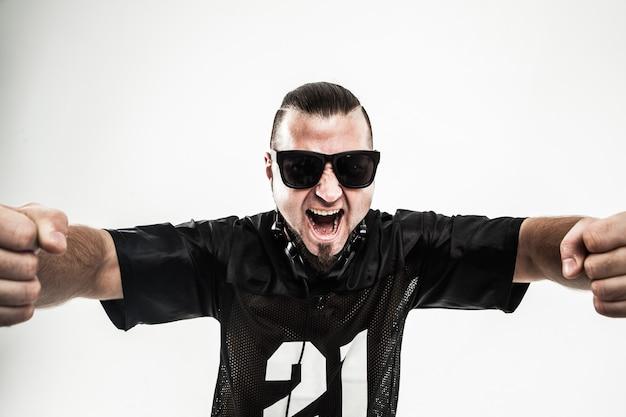 Rapero rudo con gafas de sol y auriculares sobre un fondo blanco.