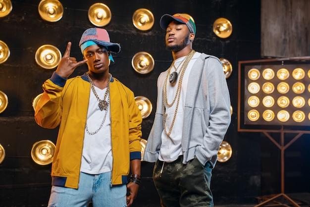 Raperos negros con gorras en el escenario con focos