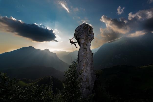 Rappel de cuerda doble de un escalador desde la punta de una roca en un paisaje de cuento de hadas