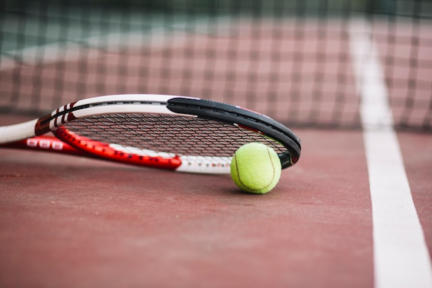 Raqueta de tenis de ángulo bajo con pelota al lado