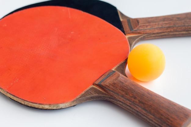 Raqueta de tenis de mesa con pelota naranja