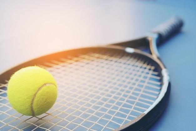 Raqueta de tenis con pelota en la cancha