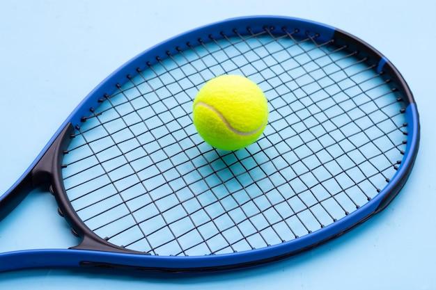 Raqueta de tenis con pelota sobre superficie azul