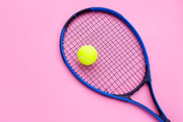 Raqueta de tenis con pelota en superficie rosa