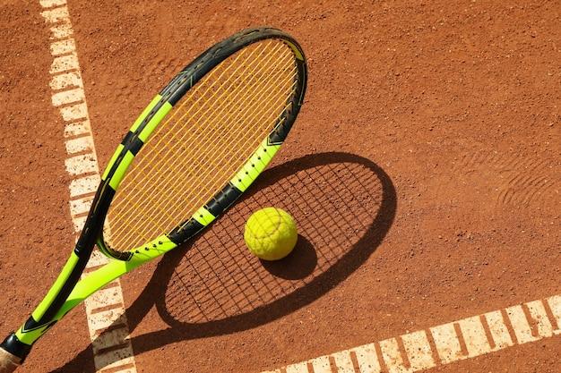Raqueta de tenis y pelota de tenis en cancha de arcilla