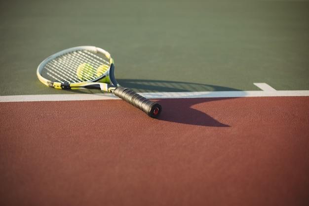 Raqueta de tenis y pelotas en la cancha
