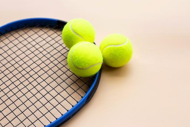 Raqueta de tenis con pelotas sobre superficie amarilla